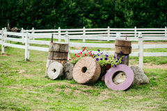 Few millstone from the windmill surrounded by flowers. Background is a corral for horses. Stock Photography