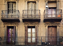 A few old-fashioned balconies. With steel fence and with different things on, placed above each other on the pastel wall with ornamental pattern Royalty Free Stock Image