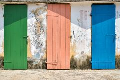 Few old wooden colorful doors on shabby light wall background stock photos