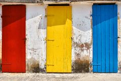 Few old wooden colorful doors on shabby light wall background stock photo