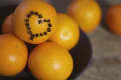 A few oranges with a heart aign made of close seeds in a gray bowl closeup on an old wooden backdround in brown with a blurred bac. Oranges with a heart sign stock image