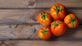 A few organic tomatoes on wood background. Natural tomatoes Royalty Free Stock Photo