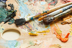 Few paintbrushes on oils artistic pallette Royalty Free Stock Image