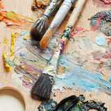 Few paintbrushes on used artistic pallette Stock Image