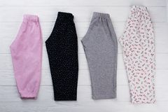 Few pairs of pants. On wooden table of clothing store. Roomy and comfy for sleep or lounge at home. Girls` pajamas Royalty Free Stock Photo