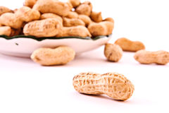 Few peanuts and dish isolated Royalty Free Stock Photos