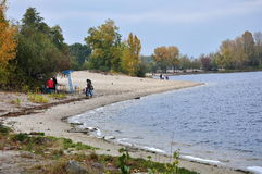 Few people walking along the river bank. Autumn landscape royalty free stock images