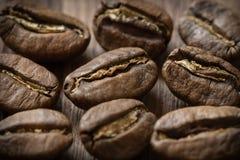 Few piec cofee fasoli na drewnianym tle Zdjęcia Stock