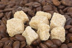Few pieces of brown sugar and coffee beans Royalty Free Stock Photo