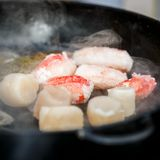 A few pieces of deep-sea scallop and several pieces of crab meat are fried in a pan.  Royalty Free Stock Photo