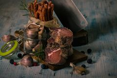 Few Pieces Of Dried Meat From Wild Boar On Cutting Board Royalty Free Stock Images