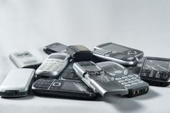 Few a pile of old broken mobile phone lying. On gray background royalty free stock photography