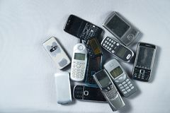 Few a pile of old broken mobile phone lying. On gray background stock photography