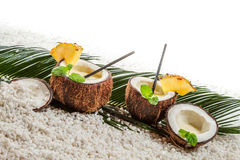 Few pinacolada drinks in coconut on white beach Stock Photo