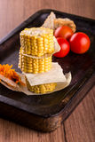 Few portions of sweet corn on a stack on wooden plate Royalty Free Stock Photography