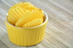 A few potato chips in yellow dish. A few ripple potato chips in yellow bowl on wooden background and shot in natural light.  Selective focus on front two chips Stock Photo