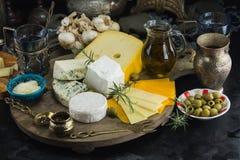 Few różni sery z oliwkami papier i oliwa z oliwek na czarnym chalkboard w kuchni typ zdjęcie stock