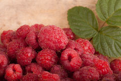 Few raspberries with leaf on wooden background Stock Images