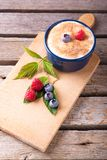 Few red and blue berries on chopping board with creamy dessert Royalty Free Stock Photo