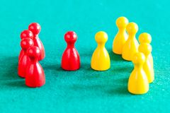 Few red pawns in front of several yellow pawns stock photo