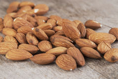 A few ripe nuts of almond are on a wooden surface. Close up photo Royalty Free Stock Photography