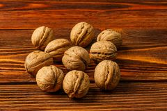 A few ripe walnuts on an old wooden background Royalty Free Stock Image