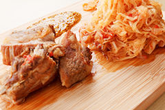 Few roasted pork ribs with tomato, carrots and cabbage on a  cutting board Stock Images