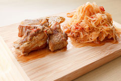 Few roasted pork ribs with tomato, carrots and cabbage on a  cutting board Royalty Free Stock Images