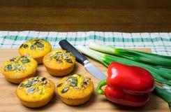 Few słodka bułeczka robić kukurydzana mąka z ziarnami, czerwony pieprz, zielona cebula, nóż, i, i na drewnianej desce zdjęcie stock