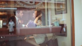 Few shots. Stylish young man and attractive young European woman in the white dress are sitting and flirting with each stock footage