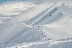 Khibiny in winter. Few skiers come down the mountain Kukisvumchorr on the background of snowy mountains. Khibiny, Russia Royalty Free Stock Photography