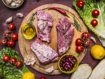 Few slices of raw beef on a cutting board, around lie ingredients tomatoes on a branch, lemon, olive oil, red hot pepper, herbs, l Royalty Free Stock Photo