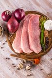 Few slices of raw pork meat on wooden plate with spices. Vertical photo of three slices of raw pork meat which are placed on dark wooden board with whole pepper Stock Image