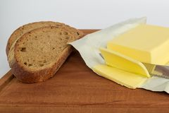 A few slices of yellow butter cut off from a large piece with a knife on a brown wooden cutting board. Several slices of rye bread royalty free stock image