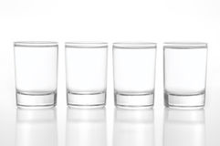 Few small shot glasses filled with alcohol on a light background. Few small shot glasses with alcohol stock photography