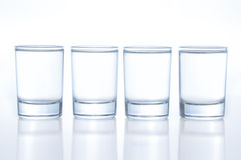 Few small shot glasses filled with alcohol on a light background. Small shots with strong alcohol stock image