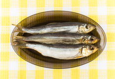 Few smoked fish in glass dish on tablecloth Stock Photo