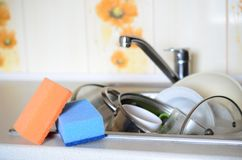 A few sponges lie on the background of the sink with dirty dishe. S Royalty Free Stock Images