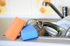 A few sponges lie on the background of the sink with dirty dishe. S Stock Photo