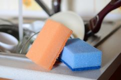 A few sponges lie on the background of the sink with dirty dishe. S Royalty Free Stock Photos