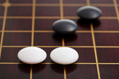 Few stones during go game playing on goban. Position of few stones during go game playing on goban close up Royalty Free Stock Image