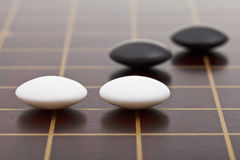 Few stones during go game playing. Position of few stones during go game playing on wooden board close up Stock Photos