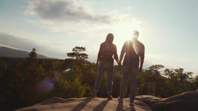 Few strzały urocza para trzyma ich ręki na wysokim skalistej góry wzgórzu otaczającym zielenią w przypadkowych ubraniach zdjęcie wideo