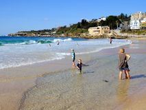 Coogee Beach, Sydney, Australia. Few swimmers at Coogee Beach, in Sydney`s Eastern Suburbs, on a fine mid-week Autumn day, with the yellow sand beach stirred up royalty free stock photos
