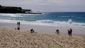 Coogee Beach, Sydney, Australia. Few swimmers at Coogee Beach, in Sydney`s Eastern Suburbs, on a fine mid-week Autumn day, with the yellow sand beach stirred up stock photo