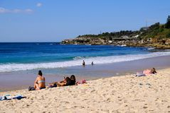 Coogee Beach, Sydney, Australia. Few swimmers at Coogee Beach, in Sydney`s Eastern Suburbs, on a fine mid-week Autumn day, with the yellow sand beach stirred up royalty free stock photo