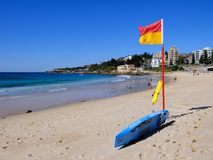 Coogee Beach, Sydney, Australia. Few swimmers at Coogee Beach, in Sydney`s Eastern Suburbs, on a fine mid-week Autumn day, with the yellow sand beach stirred up royalty free stock photography