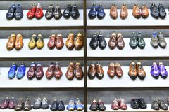 Colorfull pairs of shoes are exposed for sale. stock photos