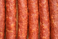 Some thin smoked sausages in a row close-up. A few thin smoked sausages in a row close up stock photos
