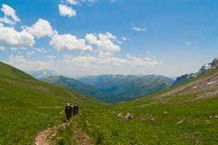 A few of tourists walking along the trail in the mountains. Royalty Free Stock Photography